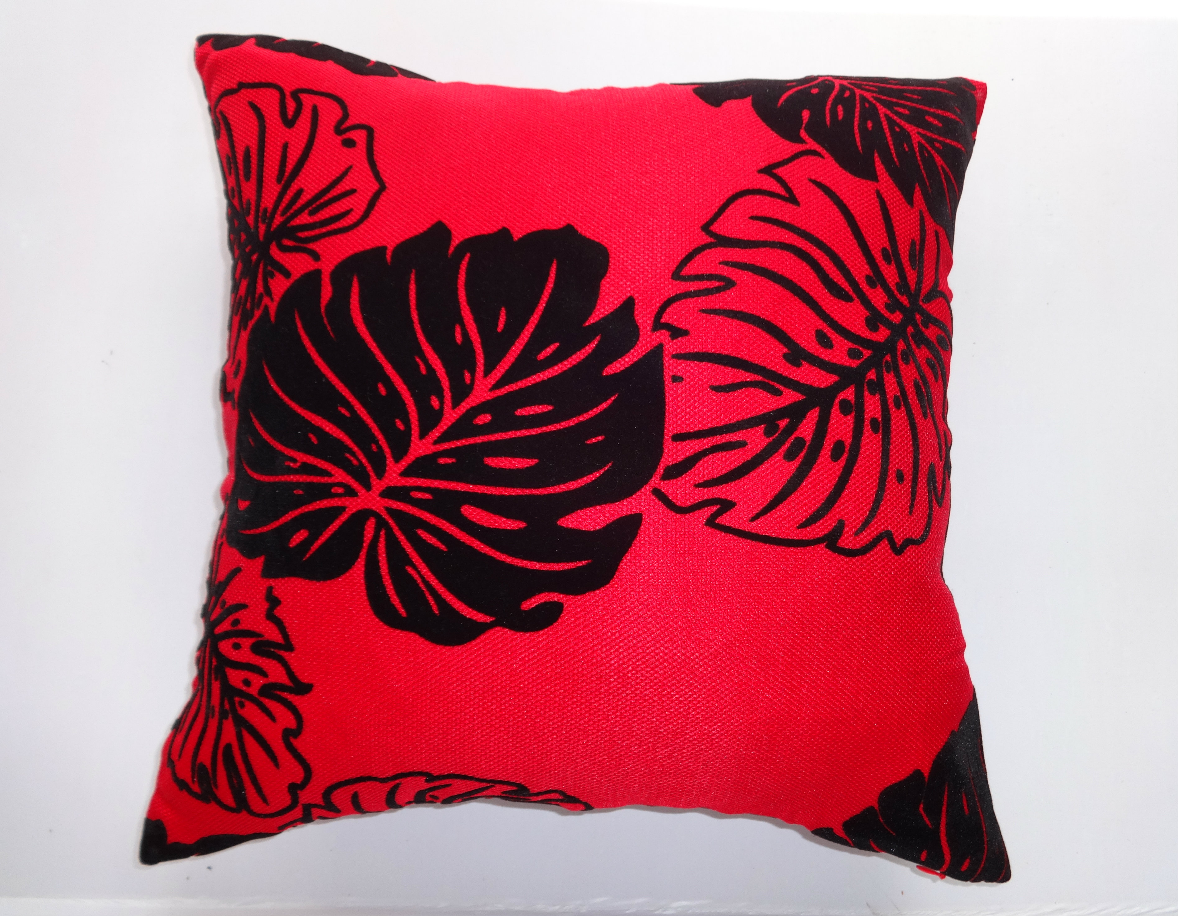 A super soft luxury black leaf medium size red cushion cover with a design that's good enough for any room. This red motif design cushion cover gives you an easy way to upgrade your sofa quickly. It's also ideal for bedrooms, living rooms, any easy-chairs and choosing in pairs adds a touch of style to any of your rooms.